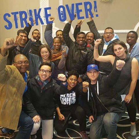 Group of people smiling with their fists raised, with blue text that says Strike Over!