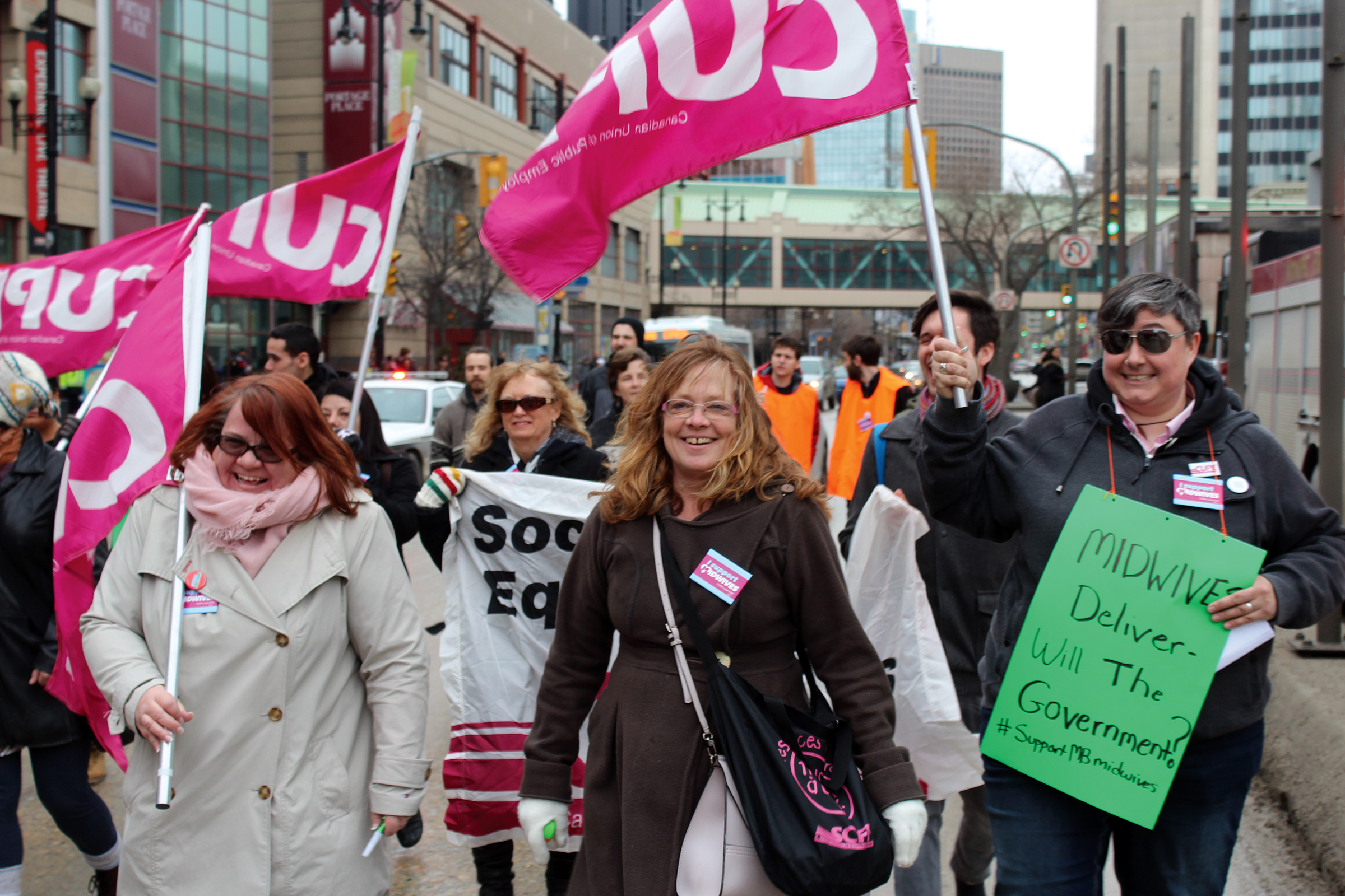 "Women march holding CUPE flags and a protest sign that says ""Midwives deliver: will the government?"""