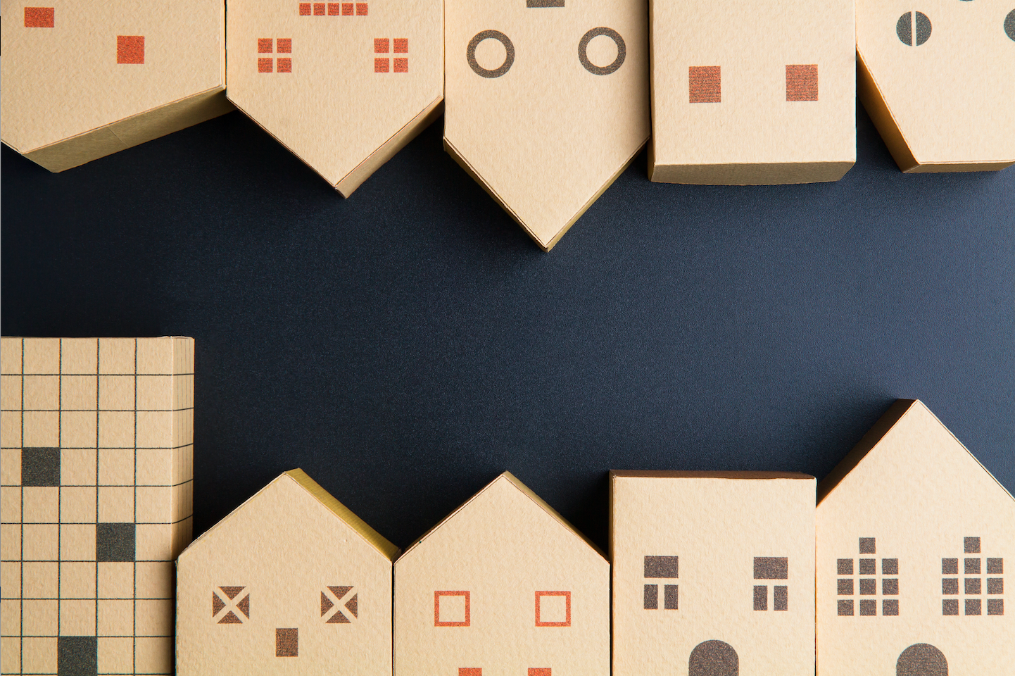 Cardboard boxes shaped like houses on a black background