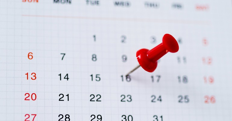 Blurred calendar page with red pushpin on 16