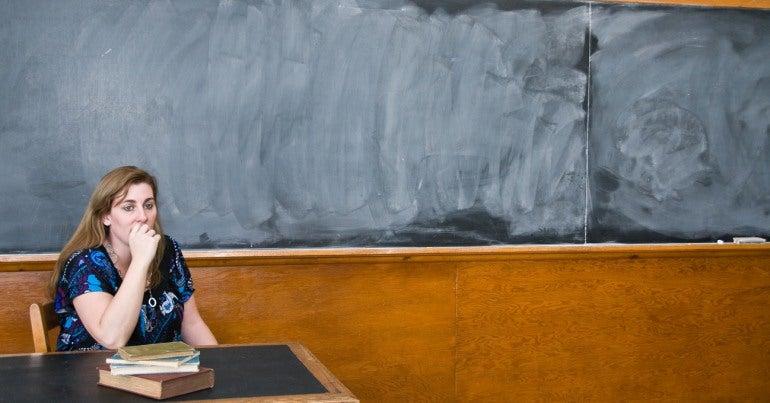 Worried female teacher at desk in front of blank blackboard
