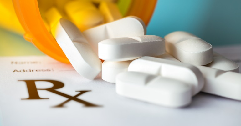 Image of white pills spilling out of an orange pill bottle onto a prescription pad