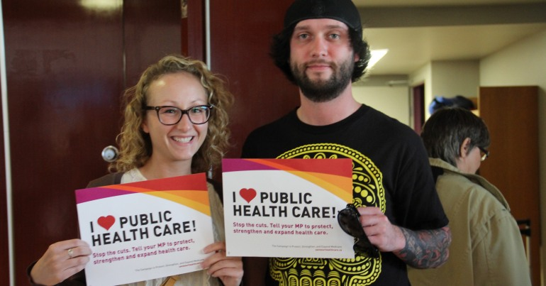 "CUPE members holding ""I <3 Public Health Care"" signs"