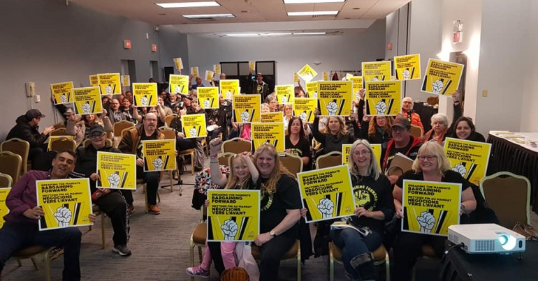 CUPE members in a meeting holding up signs