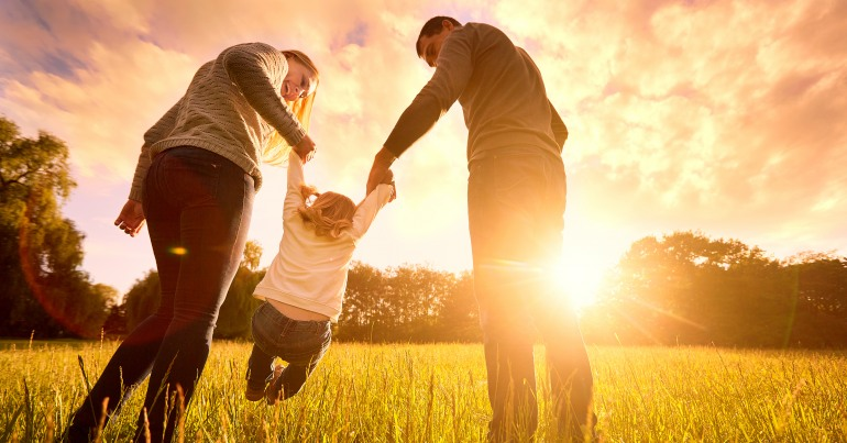 A child holds two adults' hands is swung between them. In the background the sun is low in the sky.