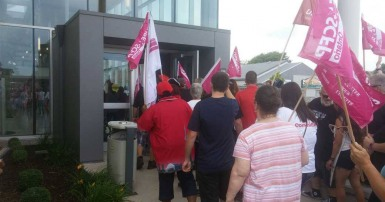 The backs of a crowd of men and women holding placards and flags, on the sidewalk in front of and entering the doorway of a grey building.