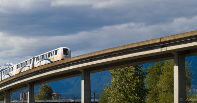 Image of Vancouver SkyTrain, elevated light rapid transit train and track with mountains and blue sky in the background.