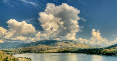 Image of lake surrounded by mountains in summer with dramatic cloud