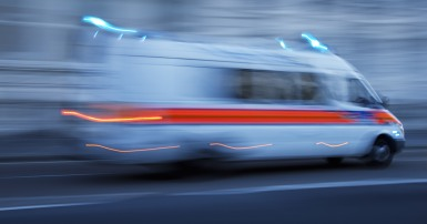 An ambulance travels so fast it is a blur