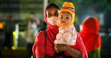 A garment worker on the way out of work with her child in Dhaka, Bangladesh.