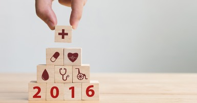 Hand arranging wood block stacking with icon healthcare medical and the year 2016