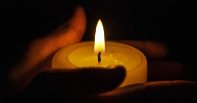 Two hands holding a small lit candle with darkness in the background