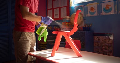 Man in red shirt  and blue gloves sprays cleaner on red children's chair