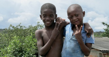 Two young boys with their arms around each other, one makes a peace sign with his fingers