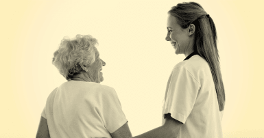 Young women with long hair wearing hospital scrubs holds the arm of an elderly woman, both smiling