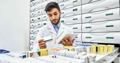 Confident male pharmacist reading label on merchandise in storage room. Young chemist is working in storage room. He is wearing lab coat at drugstore.