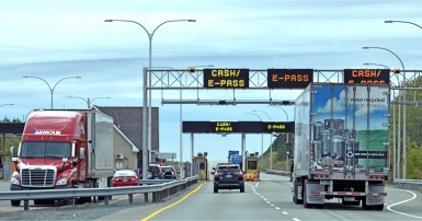Cars and trucks on a toll road with signs that say Cash/E-Pass