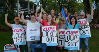 Pacific Blue Cross workers wearing signs that say lockout