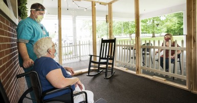 Long-term care worker in a mask and face shield stands next to an elder mask-wearing woman sitting in a wheelchair, speaking to a masked woman sitting outside a screened-in porch.