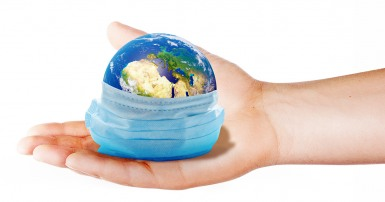 Une main qui tient la Terre avec un masque