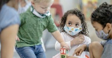 Children playing wearing masks