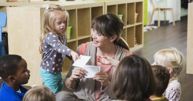 Child care worker surrounded by children, handing something to a girl with Down syndrome