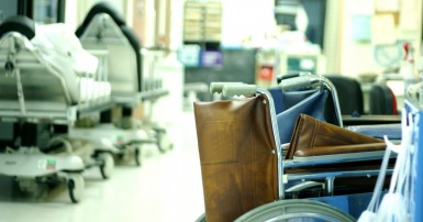 Photo of a hospital room with empty wheelchairs in the foreground and empty gurneys in the background.