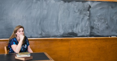 Photo of worried female teacher at desk in front of blank blackboard
