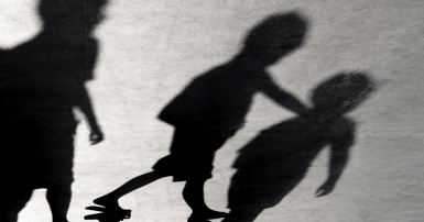 Shadows of three children on a grey concrete surface with cracks