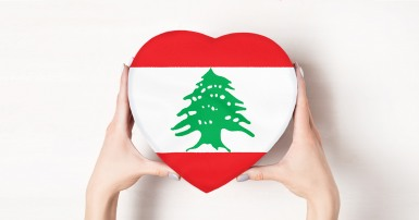 Female hands holding a heart shaped box bearing the Lebanese flag