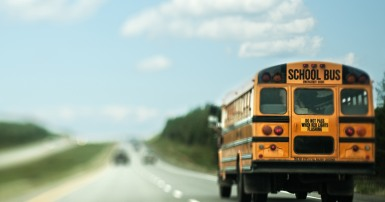 A school bus traveling down a highway. Photographed with a tilt-shift lens.