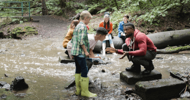 Students listen to instructor by a water stream in a forest