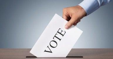 Voter puts ballot in ballot box