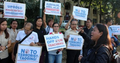 "Alliance of Concerned Teachers rally in the Philippines with signs that  say ""No to terrorist tagging""and ""Hands off our teachers."""