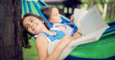 Two children reading in a hammock