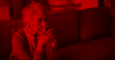 Photo of an elderly woman with a worried expression and a red overlay