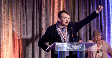 Rory Gill raises fist at CUPE AB convention