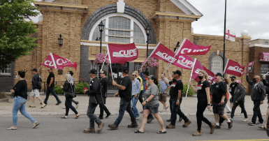 CUPE 1349 members carrying CUPE flags march in front of town hall in Grand Falls-Windsor NL