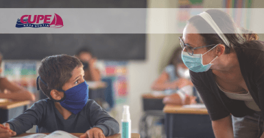 Web banner. Image: Teacher talking to young student at his desk. Both are wearing a face mask. CUPE NS logo.