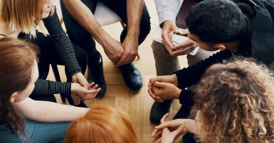 High angle of a group of teenagers sitting in a circle during group therapy