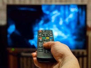 Une main, tenant une télécommande, pointée vers un téléviseur