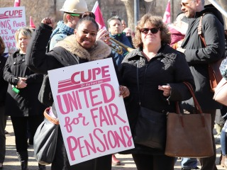 Two women at a CUPE 1975 rally, one holds a sign that says United for Fair Pensions