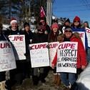 Group of men and women in winter clothing, wearing CUPE strike signs with slogans