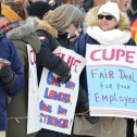 Crowd of women in winter coats and carrying CUPE strike signs