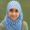Image: Young girl with a blue and white head scarf on a green background