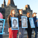 Indigenous girls hold up images of missing and murdered Indigenous women in front of Parliament
