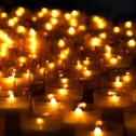 Many lit candles against a black background