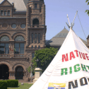 A tipi sits in front of Queen's Park