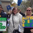 Two women and one man hold autism activism signs at a protest