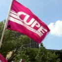 Pink CUPE flag against a blue sky